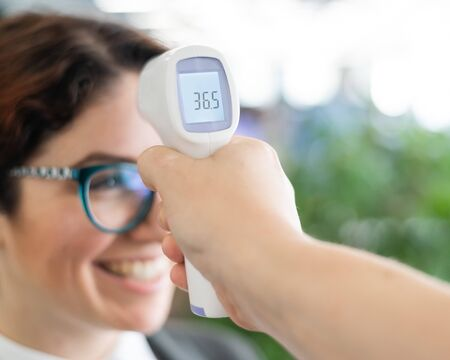 Photo pour Mandatory measurement of a fever non-contact thermometer gun of all office workers. Happy woman with normal body temperature. Infrared portable device needed during an epidemic. - image libre de droit