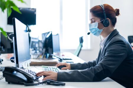 Photo pour A woman wearing a medical mask in an open space office. A female secretary answers headset clients calls. Social distance at work. Sanitary standards in the epidemic of coronavirus. - image libre de droit