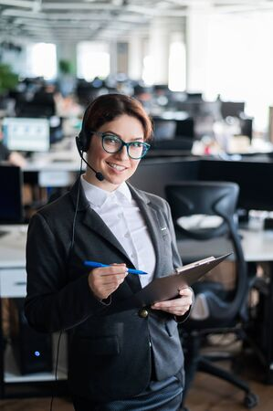 Photo for A friendly support woman with glasses and a business suit is talking on a headset with a customer. A girl with a folder in her hands stands in an open space office and answers the call with a smile. - Royalty Free Image