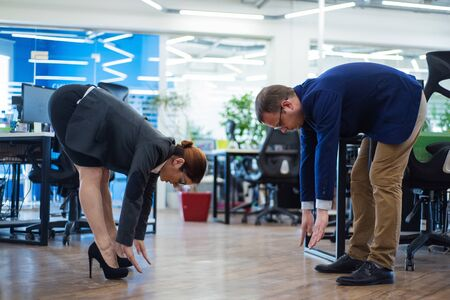 Photo for Colleagues play sports during the break. Health care concept at work. Middle managers in business suits doing fitness exercises in an open space office. Change of activity is the best rest. - Royalty Free Image