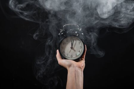 Photo for Close-up of a female hand holding a clock on a black background in smoke. Alarm clock at midnight in a mystical fog. - Royalty Free Image