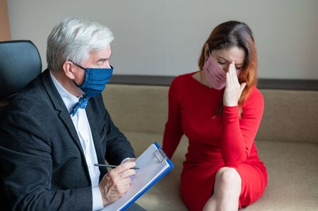 Male psychotherapist advises a female client in a medical mask. Moral support during the epidemic. Depressed woman on a visit to a psychologist. Treatment of panic attacks in the coronavirus.
