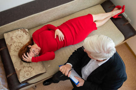 Photo pour A male psychotherapist writes on a clipboard during a patient consultation. Top view of an emotional woman lying on a couch and talks about her problems to a psychologist in a session. - image libre de droit