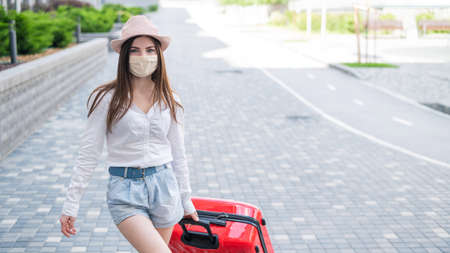 Photo pour A beautiful young Caucasian woman in a medical mask walks down the street with a red suitcase. A girl with luggage travels alone during the height of the coronavirus epidemic. The empty city. - image libre de droit