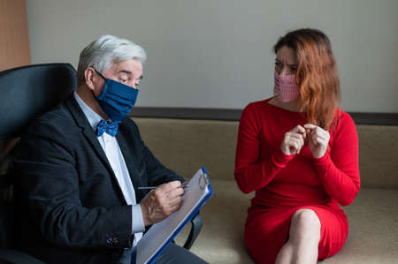 The therapist advises a female client in a medical mask. Moral support during the epidemic. Red-haired woman in a red dress at a visit to a psychologist. Treatment of panic attacks in the coronavirus.