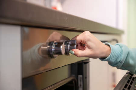 Photo pour A young woman opens the oven. Housewife includes a built-in oven. Girl is cooking pastries. - image libre de droit