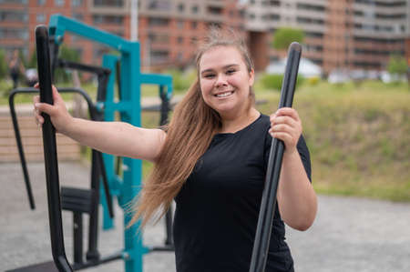 Beautiful smiling overweight young woman does fitness on an ellipsoid simulator outdoors. Fat girl is training on the sports ground for weight loss. Sport outside on a warm summer day.