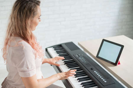 Photo pour A woman watches video lessons on a digital tablet and plays on an electro synthesizer. The girl learns to play the piano remotely. - image libre de droit