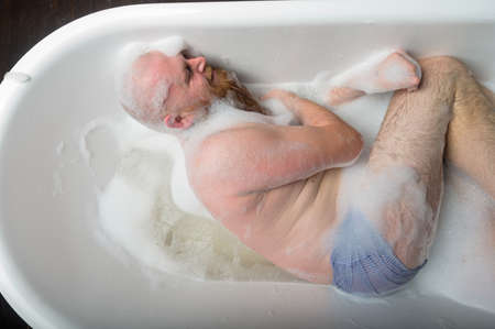 Photo pour Top view of a bald man with a red beard splashing in the foam bath. Humorous photo. A parody of glamorous girls. - image libre de droit