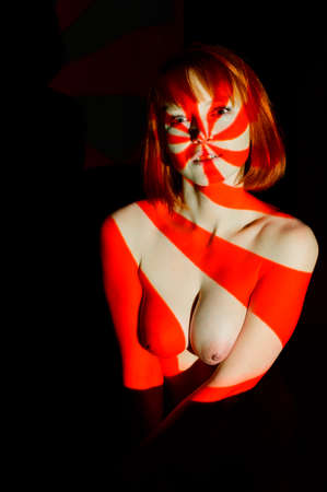 Photo for Portrait of a beautiful naked woman in the red beams of the projector. - Royalty Free Image