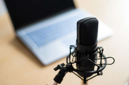 Photo for Close-up of a professional microphone on the background of a laptop. Radio broadcasters desktop - Royalty Free Image