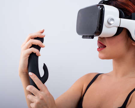 Foto de Caucasian red-haired woman wearing virtual reality glasses holding black dildo and looking lustfully. - Imagen libre de derechos