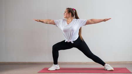 Photo pour Young fat woman doing flexibility exercises on a white background - image libre de droit