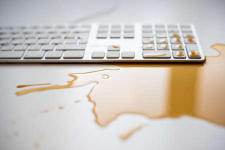 Photo pour Spilled drops of black coffee on a white computer keyboard - image libre de droit