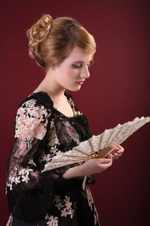 pretty young lady  in old time ball dress with fan in  style of the end of XIX century