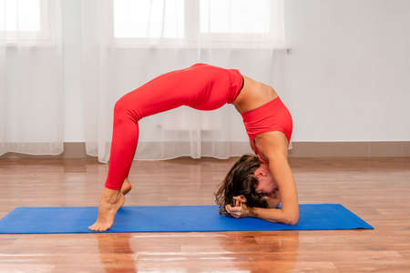 Photo pour A beautiful sportive girl is engaged in yoga, pilates, exercises, body training. A woman in a red sports uniform against the background of the training hall. Healthy lifestyle concept. - image libre de droit