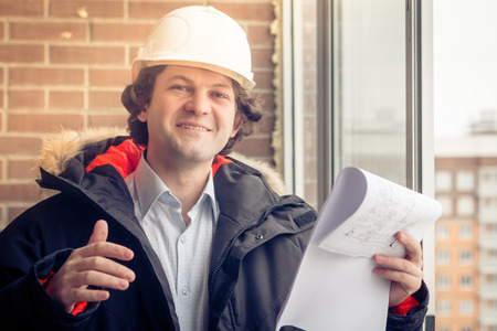 Portrait of cheerful young worker wearing hardhat posing looking at camera and smiling enjoying work on brick background. Soft focus, toned.