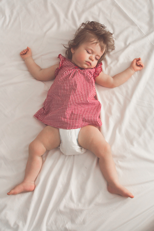 Foto de Baby girl sleeping on back with open arms and without pacifier in a bed with white sheets. Peaceful sleeping in a bright room. Pastel retro toned. Soft focus - Imagen libre de derechos