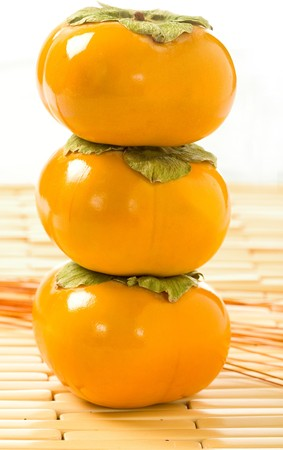 Fuyu persimmons stacked vertically.