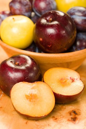A variety of plums and pluots in a bowl