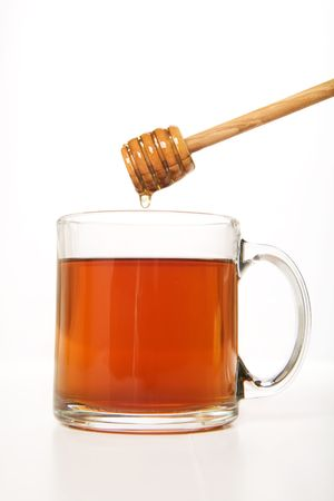 Fresh honey dripping from dipper into hot tea