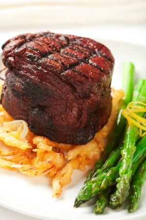 Thich Filet mignon served with crispy onions and asparagus