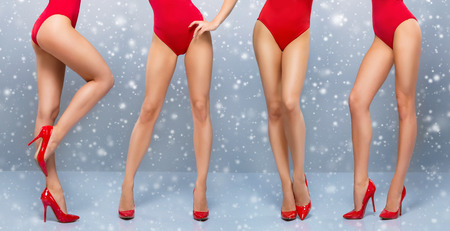 Beautiful legs of young and sporty woman in red swimsuit over the Christmas background with a snowflakes