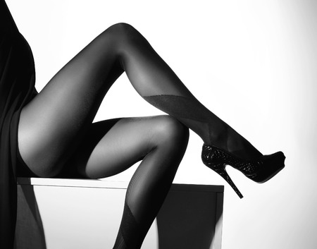 Photo pour Black and white photo of the beautiful legs in nice stockings over white background - image libre de droit