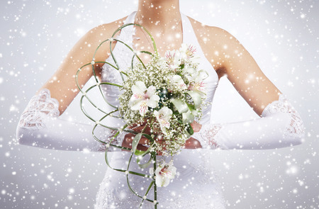 Foto de Beautiful wedding bouquet in bride's hands. Winter background with a snowflakes. - Imagen libre de derechos