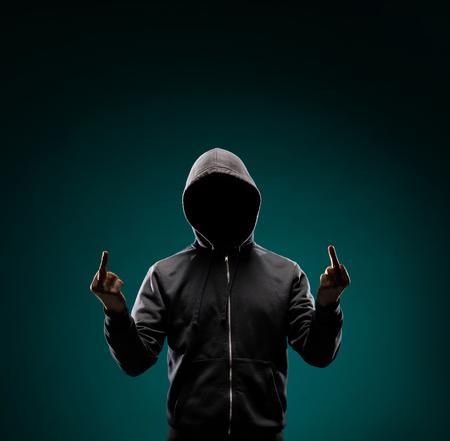 Foto de Computer hacker in hoodie. Obscured dark face. Data thief, internet fraud, darknet and cyber security concept. - Imagen libre de derechos