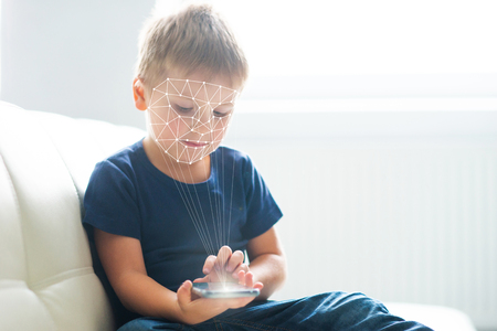 Foto de Little boy using face id authentication. Kid with a smartphone. Digital native children concept. - Imagen libre de derechos