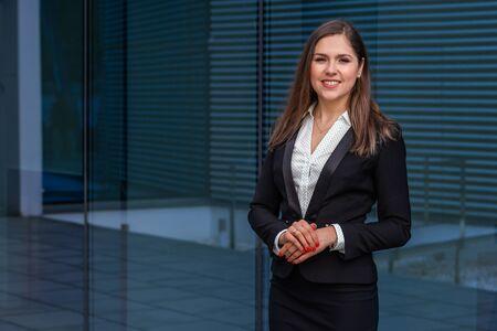 Foto de Confident businesswoman in front of modern office building. Business, banking, corporation and financial market concept. - Imagen libre de derechos