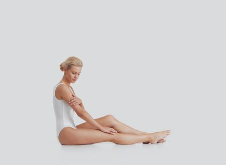 Photo pour Young, beautiful, fit and natural blond woman in white swimsuit applying moisturizing cream. Massage, skin care, cellulite removal, sport and weight loss. - image libre de droit