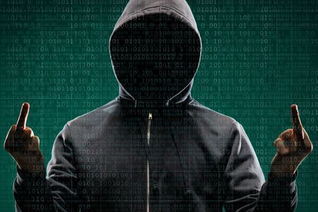 Photo pour Dangerous hacker over abstract digital background with binary code. Obscured dark face in mask and hood. Data thief, internet attack, darknet fraud, virtual reality and cyber security. - image libre de droit
