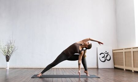 Photo pour Young and fit woman practicing yoga indoor in the class. Stretching exercise in the day light. Sport, fitness, health care and lifestyle concepts. - image libre de droit