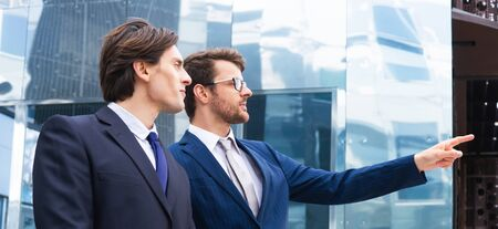 Photo pour Teamwork and business concept. Confident businesspersons having conversation about banking and financial markets in front of office building. - image libre de droit