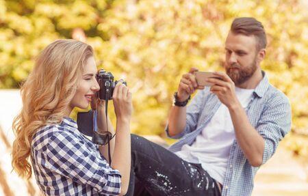 Foto de Man and woman taking photos with a camera and a smartphone in autumn park. - Imagen libre de derechos