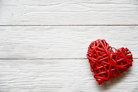 Photo pour Big red rattan heart on a white wooden background. Close-up. Top view. Valentines Day background. - image libre de droit