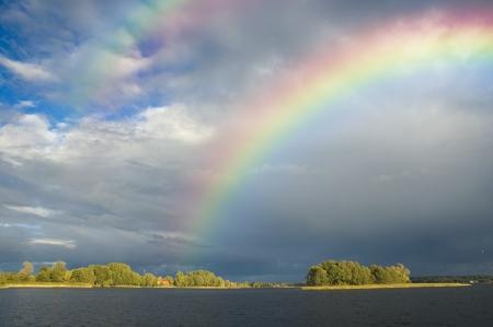Rainbow over a small sunlit island, Masuria district, Poland