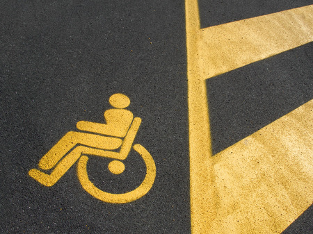 Yellow disabled parking on dark asphalt with marked area