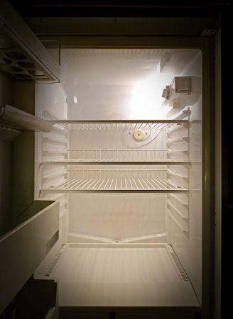 Interior of an empty fridge lit by the internal lamp