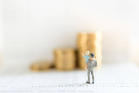 Photo pour Business, Money, Saving, Security and Family Concept. Close up of father and child standing on bank passbook and looking to stack of gold coins with copy space. - image libre de droit