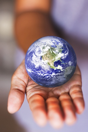 image composite of earth on palm, for earth environmental or conceptual usage.