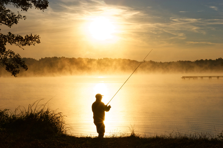 Photo pour Silhouette of fisherman standing in a lake and catching the fish during foggy sunrise - image libre de droit