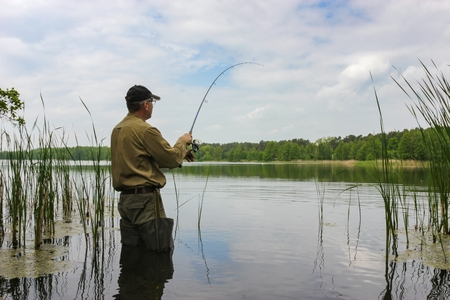 Photo pour Angler catching the fish in lake - image libre de droit