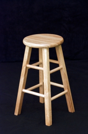 Wooden stool on black background