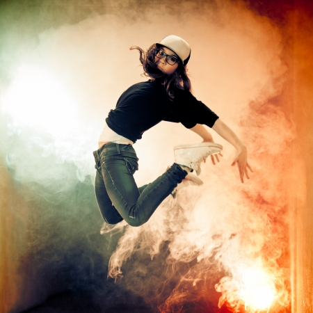 Teenage brakedancer girl jumping in a smoke