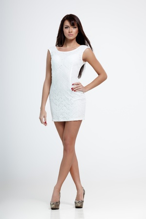 Young beautiful female model in white dress on gray background