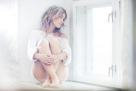 Photo pour Beautiful lady sitting by the window - image libre de droit