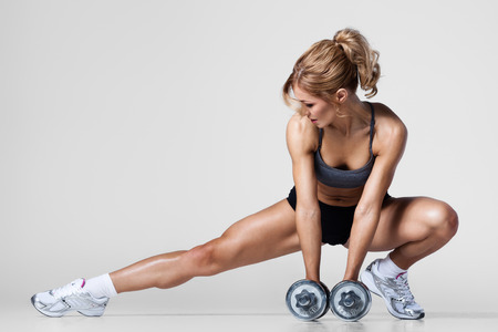 Smiling athletic woman pumping up muscules with dumbbells and stretching legs